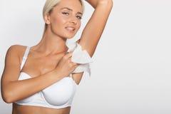 Junge Frau säubern die Achselhöhle mit Feuchtpflegetüchern Lizenzfreies Stockfoto