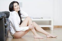 Junge Frau saß auf dem Fußboden im Sitzenraum Lizenzfreies Stockfoto