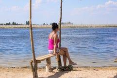 Junge Frau saß auf einer Bank, die heraus zum Meer schaut Lizenzfreies Stockfoto