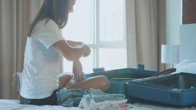 Junge Frau sammelt einen Koffer Der Reisende, der für Reise sich vorbereitet stock video footage