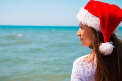 Junge Frau in Sankt-Hut auf tropischem Strand Usb-Weihnachtsbaum schloß an einen Laptop in einem leeren Büro an Weihnachtsstrand- stockfotografie