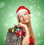 Junge Frau in Sankt-Hut mit Weihnachtsattributen und -geschenken Lizenzfreies Stockfoto