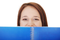 Junge Frau schaut über geöffnetem Anmerkungsbuch. Lizenzfreies Stockbild