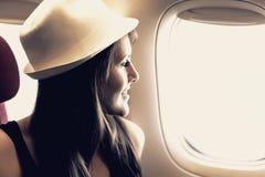 Junge Frau schaut durch ein Fenster in den Flugzeugen Lizenzfreie Stockbilder