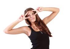 Junge Frau schaut durch zwei Zeichen Frieden Lizenzfreie Stockbilder