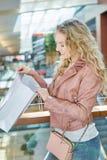 Junge Frau schaut in ihrer Einkaufstüte stockbild