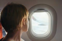 Junge Frau schaut zur Belichtungseinheit eines Flugzeuges während des Fluges Stockfotos