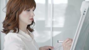 Junge Frau schreibt auf das whiteboard, das in modernes Büro steht stock footage