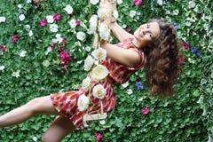 Junge Frau schwingt auf dem Schwingen, das mit Blumen überwältigt wird lizenzfreies stockfoto