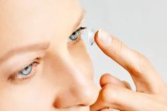 Junge Frau setzt Kontaktlinse in ihr Auge ein Eyewear, Sehverm?gen und Visions-, Augenpflege- und Gesundheits-, Augenheilkunde- u lizenzfreie stockfotos