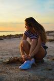 Junge Frau Sexi, die auf Strand durch das Meer sitzt Stockbilder