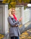 Junge Frau simsende sms im schönen Herbstpark Stockbilder