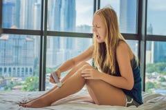 Junge Frau sitin auf Bett zu Hause und epilation mit epilator auf Beinen tuend und ist in den Schmerz Auf dem Hintergrund eines F stockbild