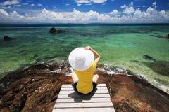 Junge Frau sitzen auf einer Brücke über Meer Stockbilder