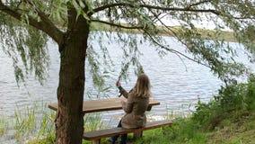 Junge Frau sitzen Bankkräuselungsseewasserspiel-Weidenbaumast stock footage