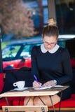 Junge Frau sitzen Café im im Freienschreibt etwas in ein Notizbuch Stockfotografie