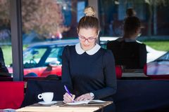 Junge Frau sitzen Café im im Freienschreibt etwas in ein Notizbuch Lizenzfreie Stockbilder