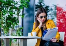 Junge Frau sitzen Zeitschrift des Cafés Lesein der im freien lizenzfreie stockfotografie