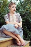 Junge Frau sitzt auf alten Jobstepps Stockfoto