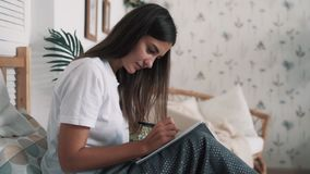 Junge Frau sitzt auf Bett und schreibt Morgenseiten in Tagebuch, Zeitlupe stock video