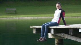 Junge Frau sitzt auf dem Dock, das ihre Beine schwingt stock footage