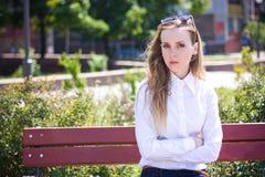 Junge Frau sitzt auf der Bank stockfotos