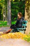 Junge Frau sitzt auf der Bank im Herbstpark Stockfotografie
