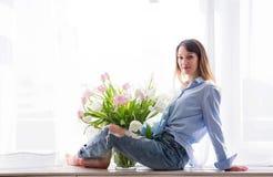 Junge Frau sitzt auf einem Fenster mit einem Blumenstrauß von Blumen stockfotos