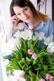 Junge Frau sitzt auf einem Fenster mit einem Blumenstrauß von Blumen lizenzfreie stockbilder