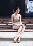 Junge Frau sitzt auf einer Bank Stockfotos