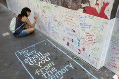 Junge Frau sitzt auf Pflasterung nahe Bodennullpunkt und schreibt auf Wand Stockbild