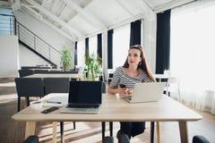 Junge Frau sitzt am Cafétisch unter Verwendung eines Laptops und des Haltens eines Handys beim mit durchdachtem Anstarren weg sch Stockbilder