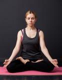 Junge Frau sitzt in der Lotoshaltung mit geschlossenen Augen Lizenzfreie Stockfotografie