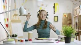 Junge Frau sitzt durch Tabelle in den Kopfhörern und in den Tänzen ein kleines stock footage