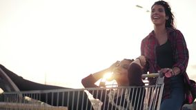 Junge Frau sitzt im Lebensmittelgeschäftwarenkorb, während ihr Freund sie hinten am Parken durch das Einkaufszentrum drückt stock footage