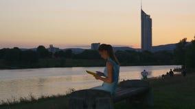 Junge Frau sitzt mit Eleser nahe dem Fluss stock footage
