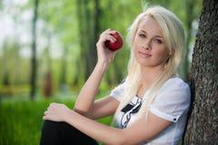 Junge Frau sitzt nahe Baum im Park Lizenzfreie Stockfotografie