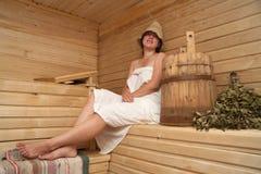 Junge Frau sitzt am Saunabad Stockfotografie