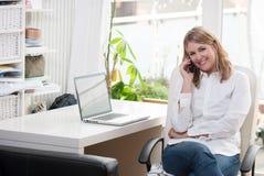 Junge Frau sitzt am Schreibtisch und an den Telefonen Stockfotografie