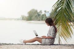 Junge Frau sitzt am Strand und arbeitet im Laptop stockfotos
