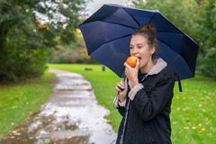 Junge Frau Smilling, die draußen Apfel isst lizenzfreie stockbilder