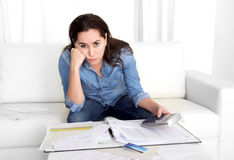 Junge Frau sorgte sich zu Hause in den Druckbuchhaltungs-bankfähigen Papieren mit Taschenrechner Stockfoto