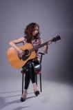 Junge Frau spielt auf einer Akustikgitarre, lokalisiert auf einem Grauwal Lizenzfreies Stockfoto