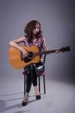 Junge Frau spielt auf einer Akustikgitarre, lokalisiert auf einem Grauwal Lizenzfreie Stockfotos