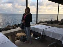 Junge Frau am Spitzenrestaurant mit Meerblick Stockbild