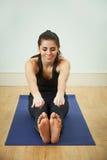 Junge Frau in Sportkleidungs-rührenden Zehen auf Matte Lizenzfreie Stockfotografie