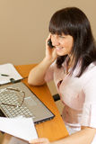 Junge Frau spricht über Mobile im Büro Lizenzfreies Stockfoto