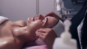 Junge Frau spricht mit ihrem Cosmetologist beim Lügen auf der Couch während des kosmetischen Gesichtsverfahrens im Badekurortsalo stock video