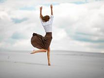 Junge Frau springt auf Sand in der Wüste Stockbilder