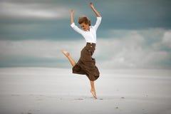 Junge Frau springt auf Sand in der Wüste und im frohen Lachen Lizenzfreie Stockbilder